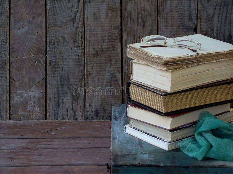 A composição de uma pilha de livros velhos e de vidros em um fundo de madeira Foto do vintage Vista lateral Copie o espaço imagem de stock