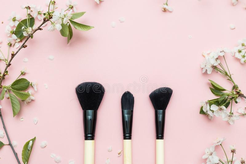 Composição decorativa da configuração do plano com escovas e flores dos cosméticos Configuração lisa, vista superior no fundo cor foto de stock royalty free