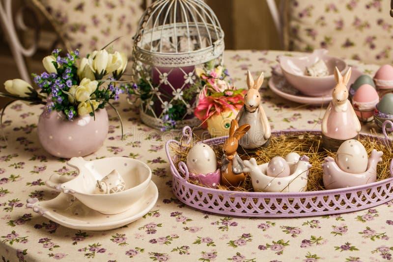 Composição decorativa da Páscoa em um fundo do vintage Mola Um vaso de flores com muscari floresce, os coelhos de uma porcelana,  foto de stock royalty free