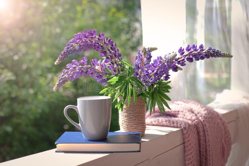 Composição delicada com o ramalhete, o copo e o livro roxos dos lupines foto de stock