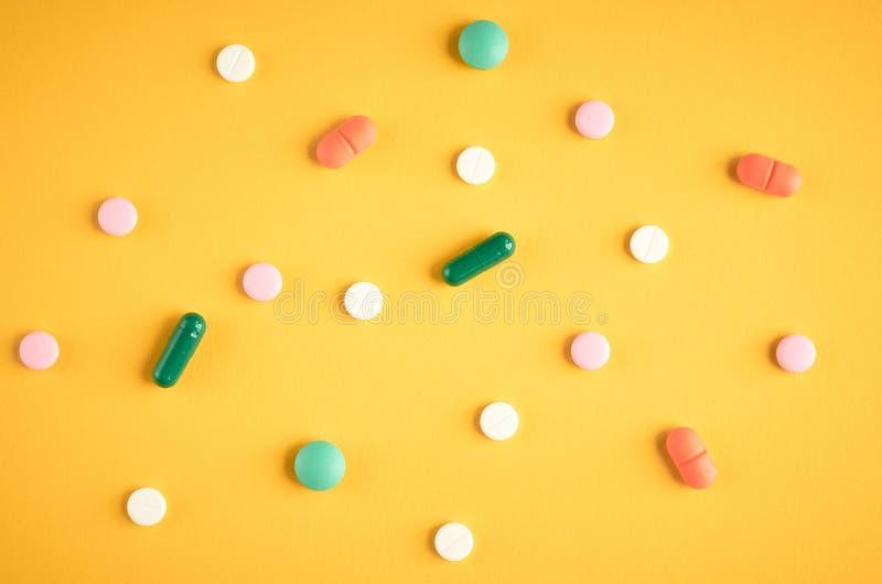 Composição diferente dos comprimidos da cor no fundo amarelo fotos de stock royalty free