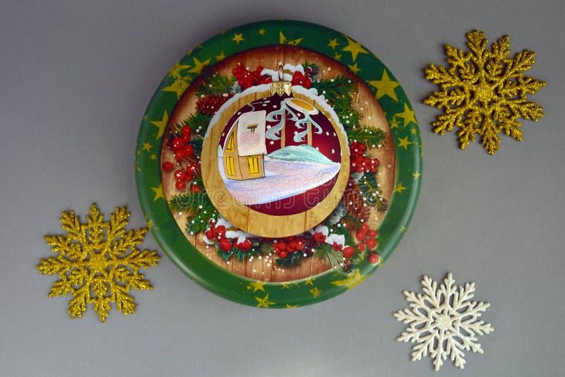 Composição do ano novo no fundo cinzento, Natal, inverno, conceito do feriado Bola do Natal com uma casa coberto de neve pintada foto de stock royalty free