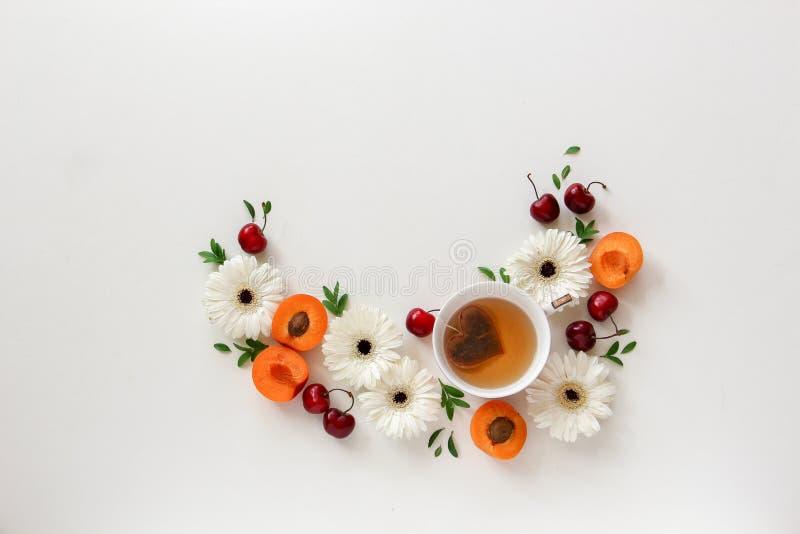 Composição do círculo das flores e dos frutos com um copo do chá com o saquinho de chá da forma do coração fotos de stock royalty free