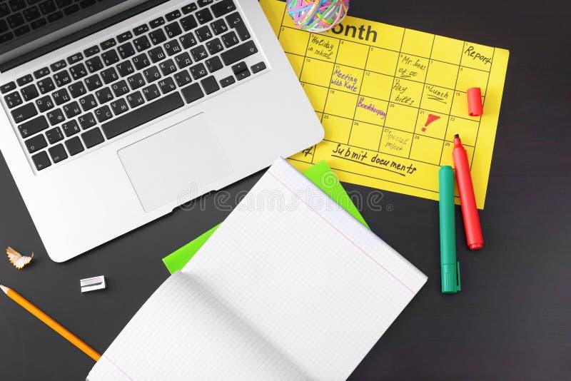 Composição do calendário com lista de afazeres e portátil na tabela escura imagens de stock