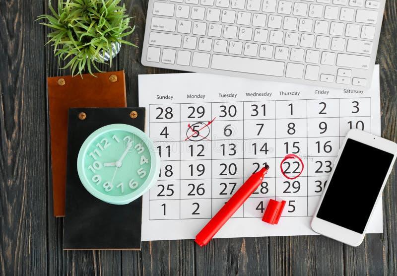 Composição do calendário com notas, teclado de computador e pulso de disparo no fundo de madeira foto de stock royalty free