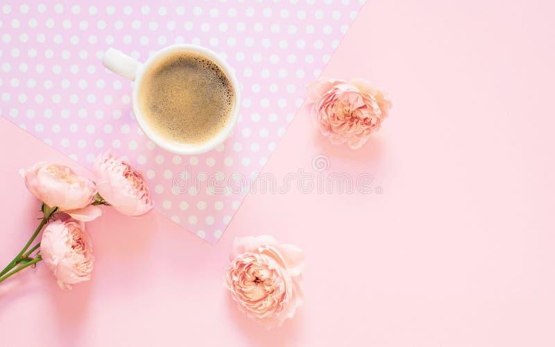 Composição do copo branco com café preto e flores em um claro - fundo cor-de-rosa imagens de stock royalty free