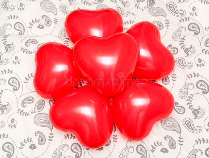 A composição do coração vermelho deu forma a balões em uma cobertura imagens de stock