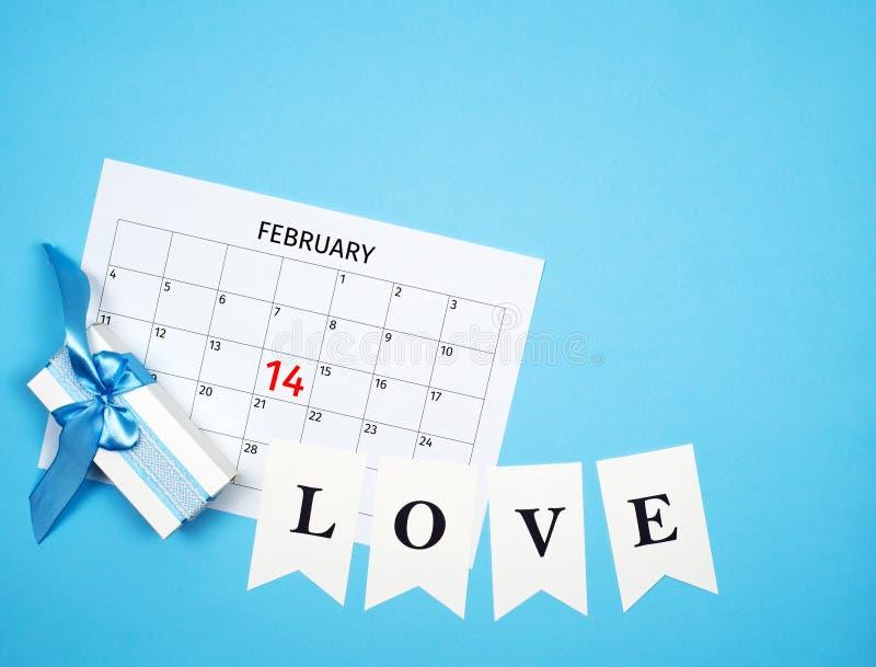 Composição do dia de Valentim com calendário, caixa de presente, festão do amor no fundo azul com espaço livre fotos de stock royalty free