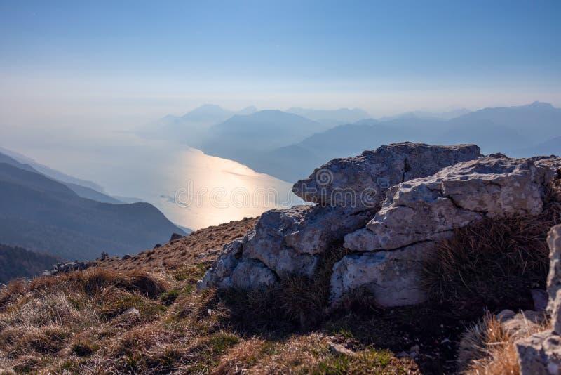 Composição do fundo das pedras e uma vista do lago Garda imagem de stock