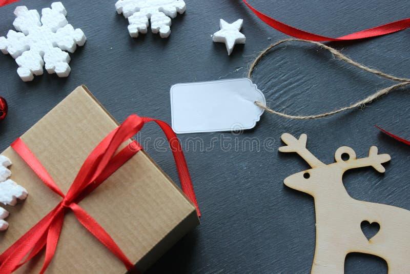 Composição do Natal Caixa de presente com a fita, madeira e os flocos de neve vermelhos do cetim no fundo preto Etiqueta, etiquet imagem de stock royalty free