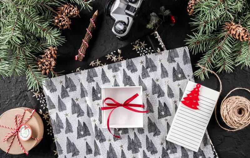 Composição do Natal com letra, xmas que envolve, ramos do abeto, caixa para os presentes, cones do pinho no fundo do feriado imagem de stock