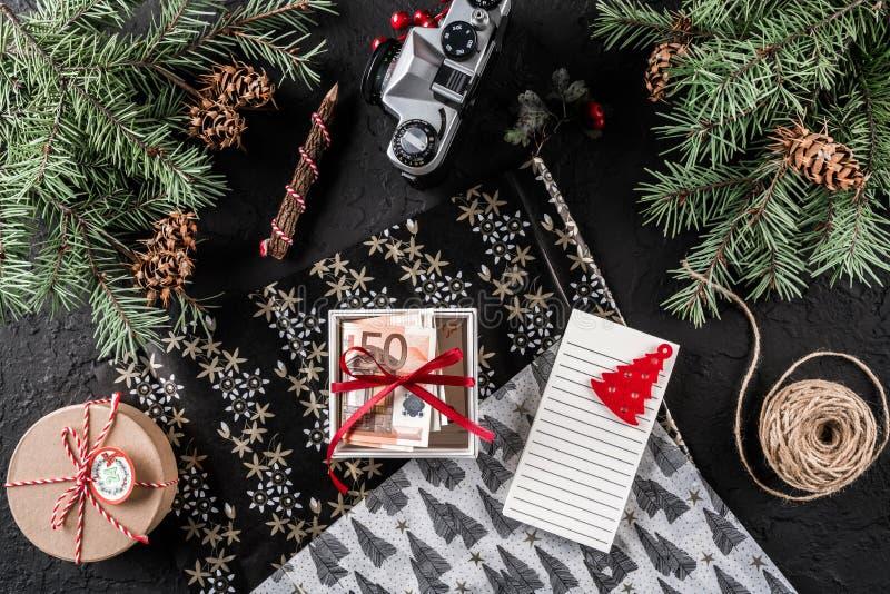 Composição do Natal com letra, xmas que envolve, ramos do abeto, dinheiro na caixa para os presentes, cones do pinho no fundo do  fotografia de stock