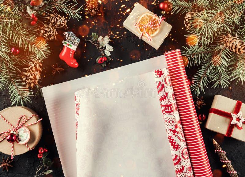 Composição do Natal com o xmas que envolve, ramos do abeto, presentes, cones do pinho, decorações vermelhas no fundo do feriado imagem de stock royalty free