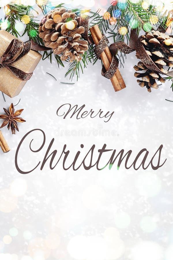 Composição do Natal e do ano novo A caixa de presente com fita, abeto ramifica com cones, anis de estrela, canela no fundo branco fotografia de stock