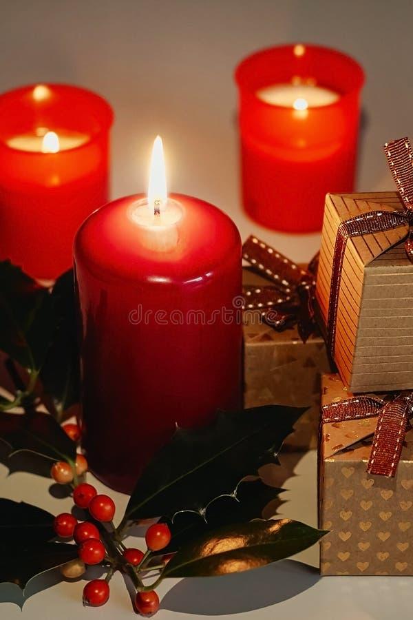 Composição do Natal e do ano novo Velas, caixas de presente e ramo do Lit do azevinho fotografia de stock royalty free
