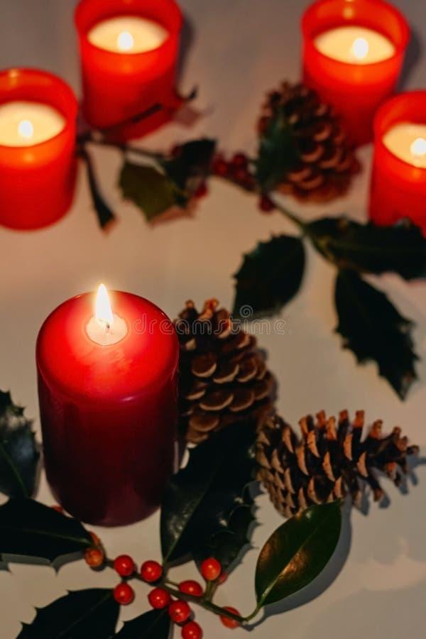 Composição do Natal e do ano novo Velas do Lit, cones de abeto e ramo do azevinho fotografia de stock