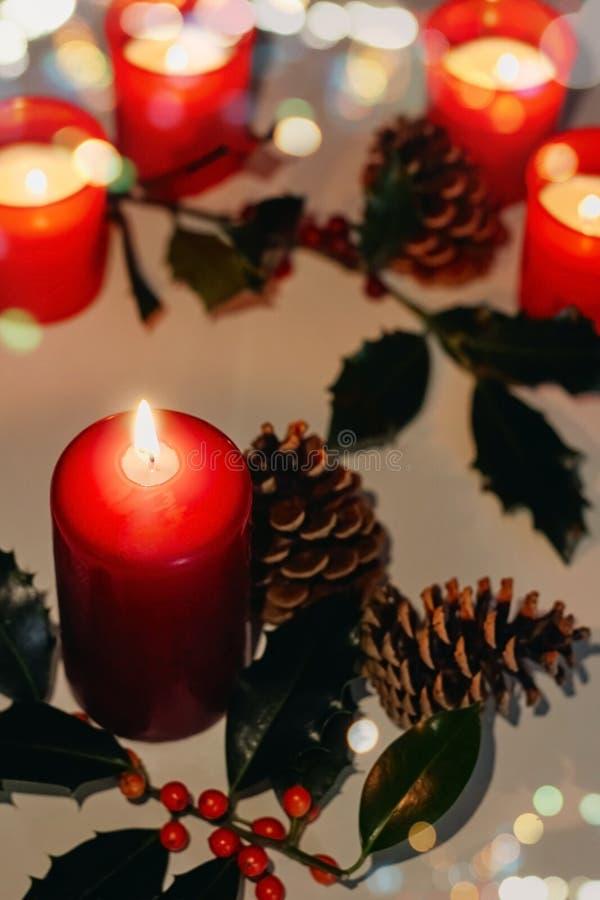 Composição do Natal e do ano novo Velas do Lit, cones de abeto e ramo do azevinho imagem de stock