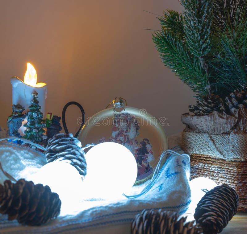 Composição do Natal ou do ano novo com gerland de queimadura, cones do pinho e as bagas vermelhas, fundo escuro da floresta, foco imagens de stock royalty free