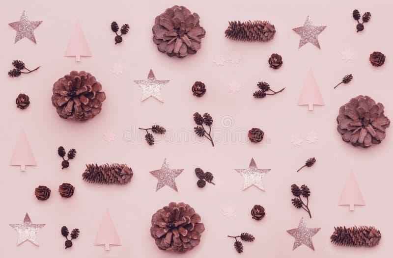 Composição do Natal Teste padrão feito de cones do pinho do Natal, de estrelas brilhantes e de árvores do xmas no fundo do rosa p imagem de stock