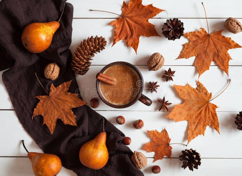 Composição do outono com latte, canela, as porcas e as folhas quentes da abóbora Conceito da manhã acolhedor, conforto, tempo da  fotos de stock royalty free