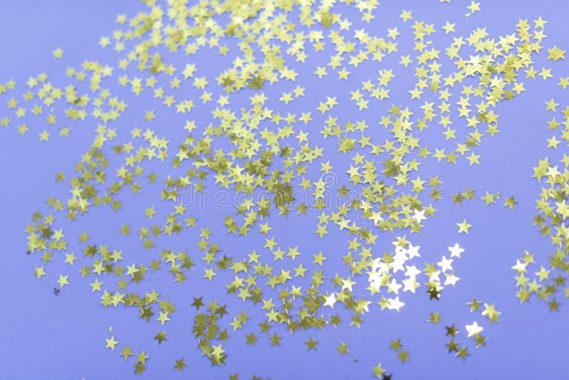 Composição do partido Decorações douradas das estrelas no fundo roxo Natal, inverno, ano novo, conceito do birtda seletivo foto de stock royalty free