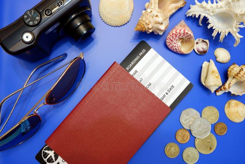 Composição do passaporte com passagem de embarque, a câmera compacta, os óculos de sol, os escudos do mar e as moedas estrangeira fotografia de stock