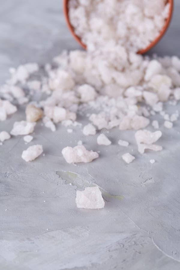 Composição do sal do mar na bacia cerâmica virada para cozinhar ou dos termas no fundo branco, vista superior, foco seletivo fotografia de stock royalty free