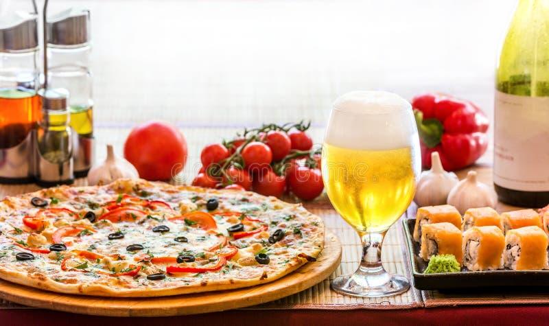 Composição do sushi e da pizza da cerveja foto de stock