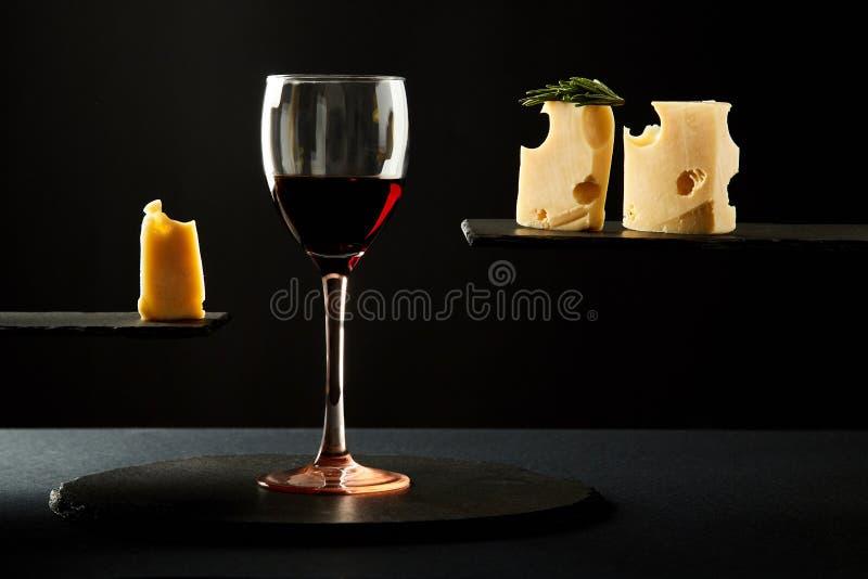 Composição do vinho tinto perfumado no vidro e nas partes de queijo duro foto de stock