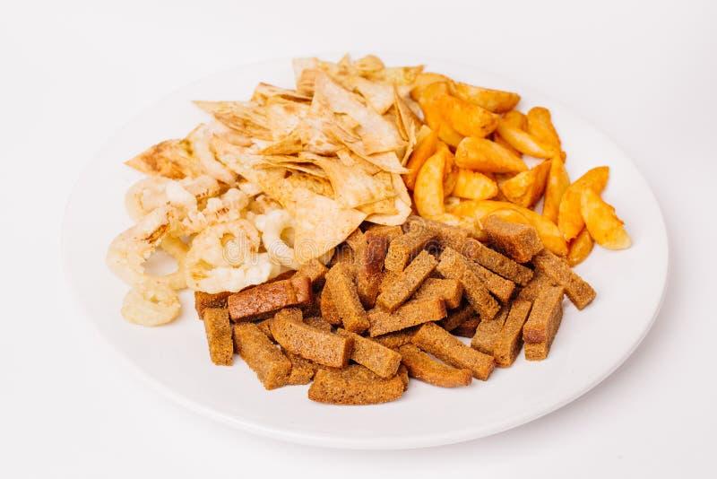 Composição dos petiscos do fast food com anéis de cebola, biscoitos, cozidos imagens de stock