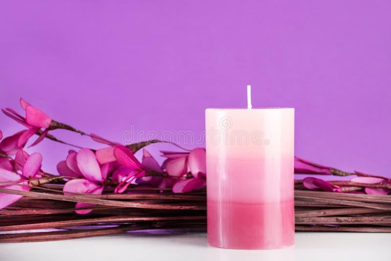 Composição dos termas com vela aromática e flores e ramos roxos na mesa fotografia de stock