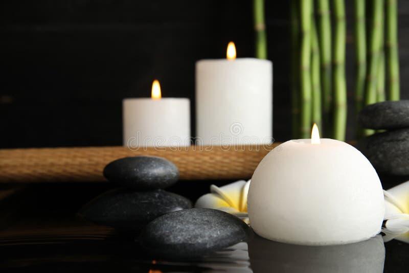 Composição dos termas com vela de queimadura na água imagem de stock royalty free