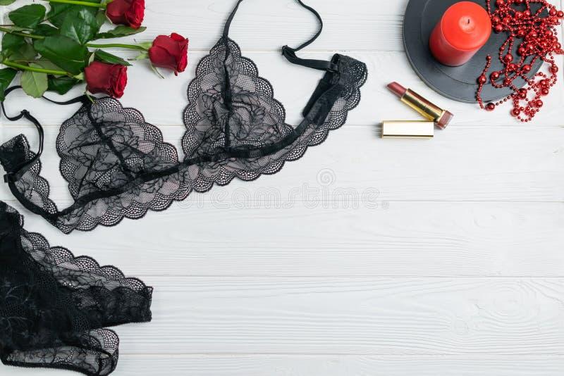 Composição elegante da roupa interior do laço preto com rosas vermelhas e vela fotos de stock royalty free