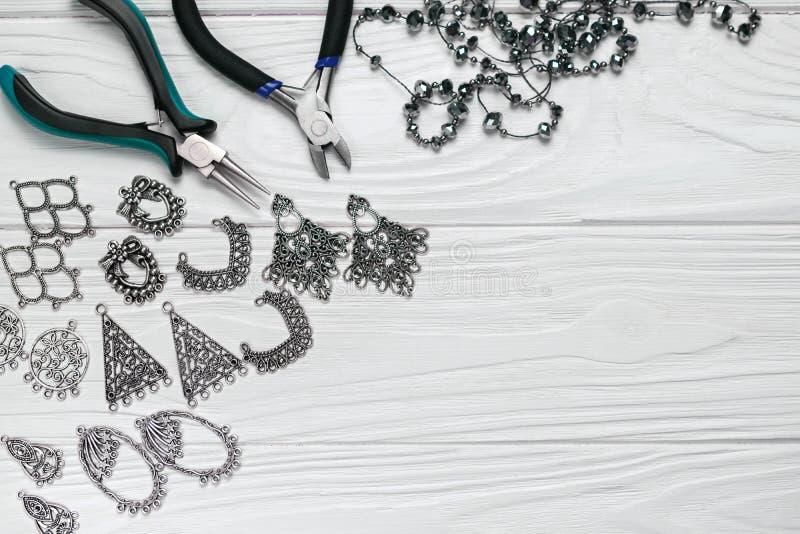 Composição feito a mão do ofício dos resultados da joia com enfeites dos grânulos dos alicates no fundo de madeira branco foto de stock