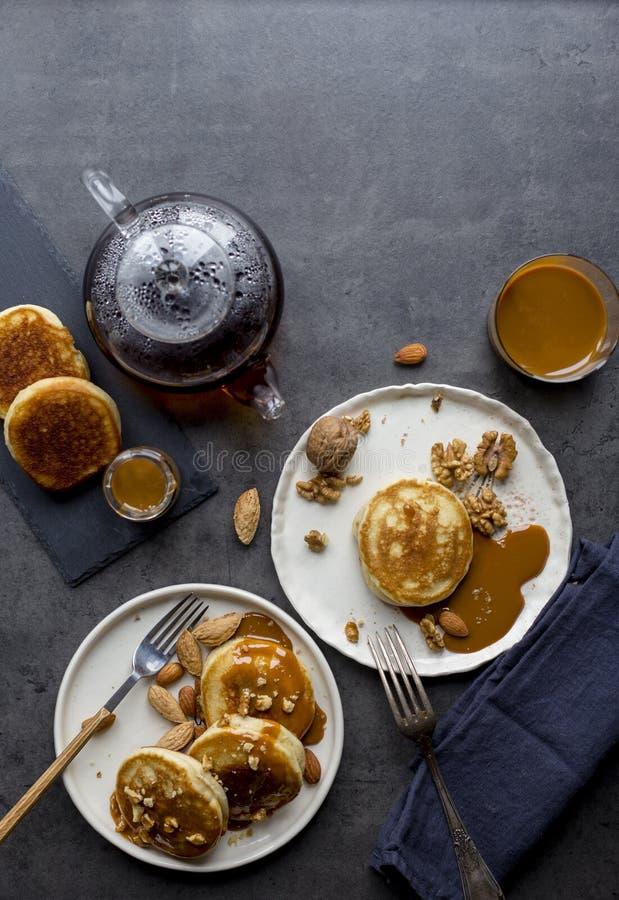 Composição festiva com panquecas e leite condensado do caramelo no fundo preto imagens de stock royalty free