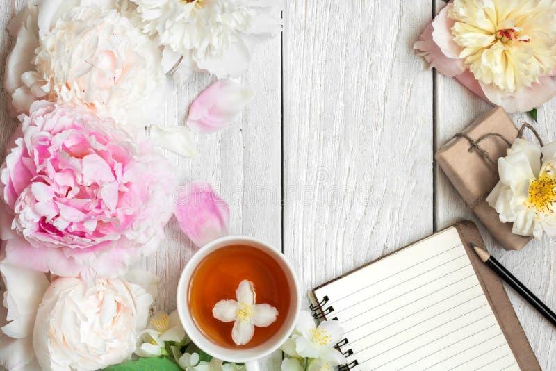 Composição festiva o copo do chá com peônia, cor-de-rosa e jasmim floresce com caixa de presente e caderno imagens de stock