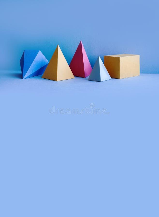Composição geométrica abstrata colorida O cubo retangular da pirâmide tridimensional de prisma objeta no fundo azul foto de stock royalty free