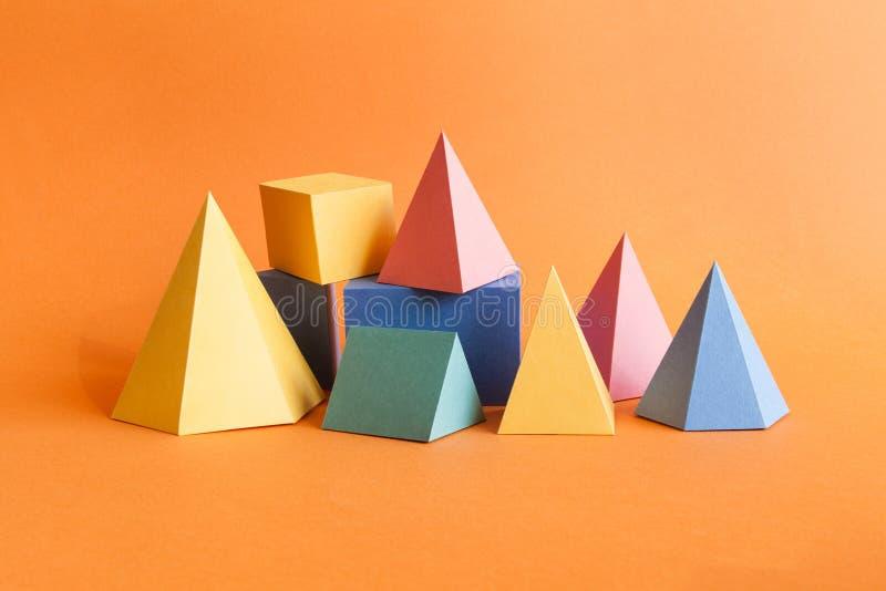Composição geométrica abstrata colorida O cubo retangular da pirâmide tridimensional de prisma objeta no papel alaranjado imagem de stock royalty free