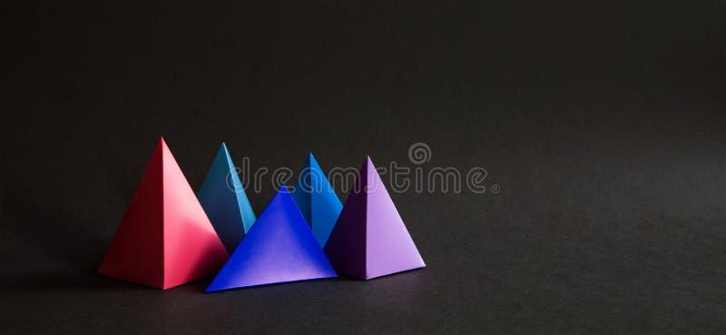 Composição geométrica colorida abstrata A pirâmide tridimensional de prisma objeta no fundo de papel preto Azul cor-de-rosa fotografia de stock