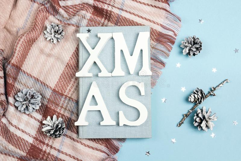 Composição invertido dos feriados de inverno com livro, manta, cones e título imagem de stock