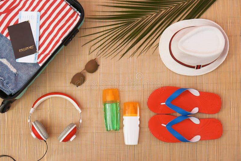 Composição lisa da configuração com artigos abertos da mala de viagem e da praia imagem de stock