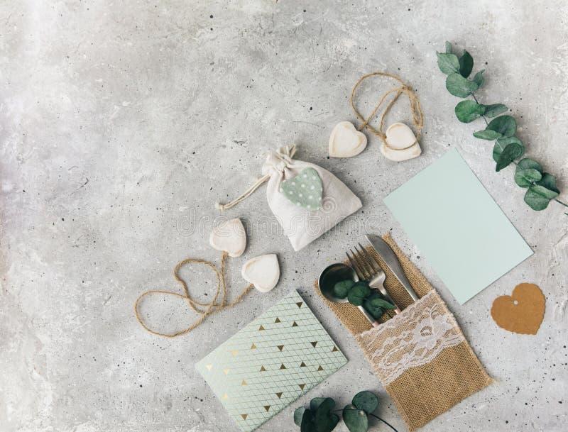 Composição lisa do casamento da configuração com cartão, decorações e eucalipto, cumprimentos, convite fotos de stock