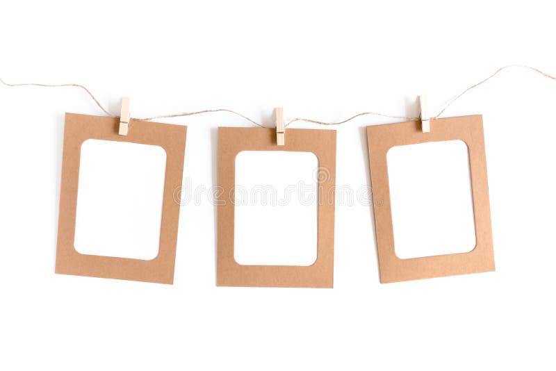 Composição mínima denominada com quadro do papel de embalagem, pregadores de roupa de madeira, corda da guita fotografia de stock
