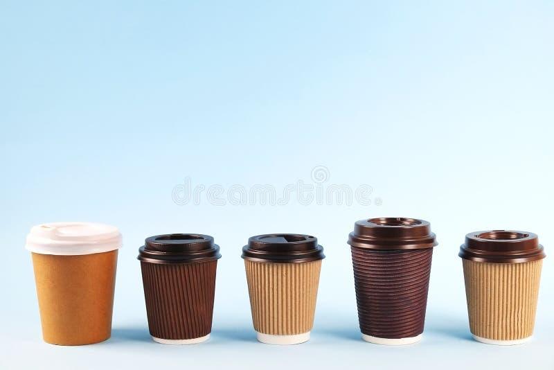 Composição mínima simplista colorida com o copo de café do papel de prova do calor Remova a caneca do chá com tampão plástico Con fotos de stock