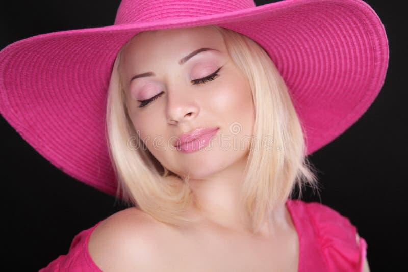 composição Mulher consideravelmente loura no chapéu cor-de-rosa isolado no backgro preto imagem de stock