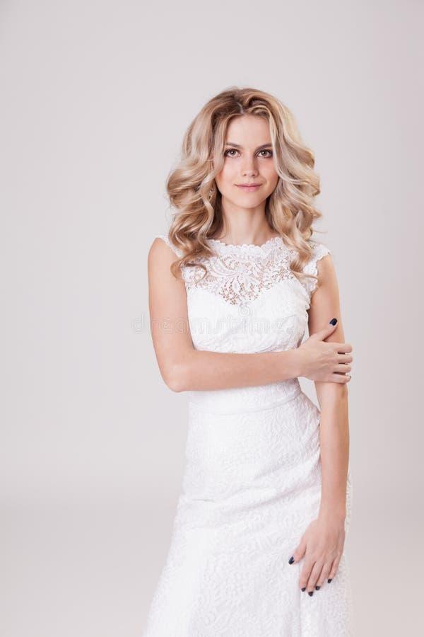 Composição, penteado e vestido do casamento Pose encaracolado nova da noiva no estúdio no fundo cinzento fotografia de stock