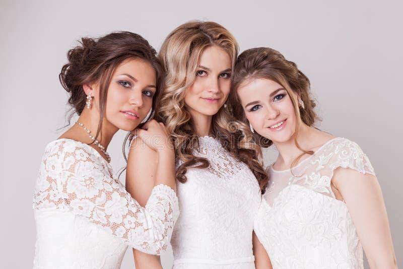 Composição, penteado e vestidos do casamento Pose de três noivas no estúdio no fundo cinzento fotos de stock royalty free
