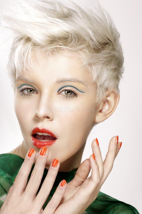 Composição perfeita e tratamento de mãos do penteado modelo louro da beleza foto de stock