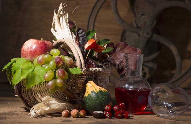 Composição pitoresca do outono com cesta, frutos, abóbora, caneca foto de stock royalty free