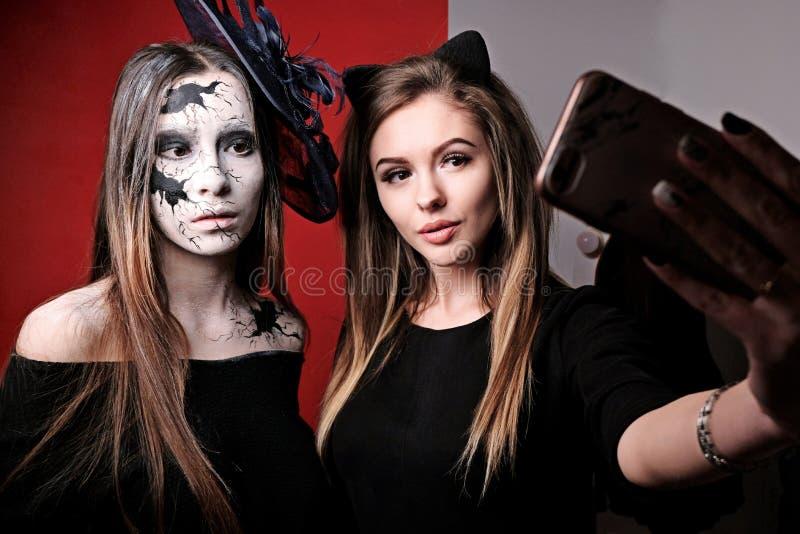 Composi??o de Halloween Duas meninas fazem selfies antes de um partido em todo o dia de Saint A imagem de uma boneca rachada foto de stock royalty free
